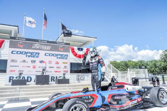 Christian Rasmussen parkerer sin racer foran podiet for at lade sig hylde efter sin anden sejr.
