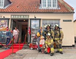Brandfolk i fuld udrustning og med »brandbil« deler brandhjelme ud til børnene.